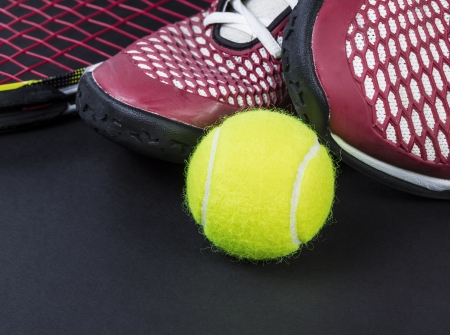 Tennis shoes, new ball, and racket on black background
