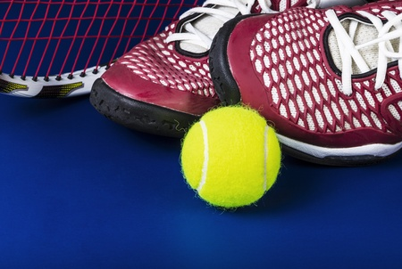 Tennis shoes, new ball, and racket on blue background