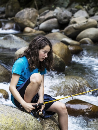 Young girl focused on fishing in remote stream with rocks and swift water in background  photo