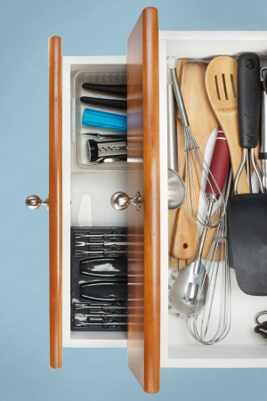 Borden georganiseerd in keukenlades op blauwe achtergrond Stockfoto