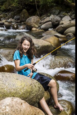 brook trout: Young girl having fun fishing barefoot on stream in woods during summer  Stock Photo