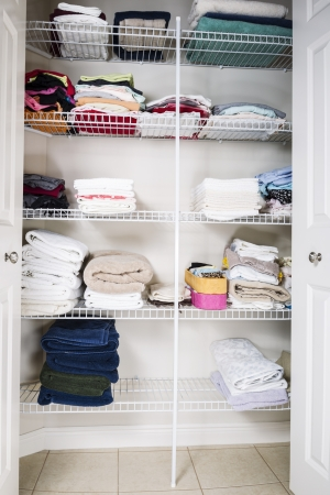 clean and organized bathroom closet with towels on shelves  photo