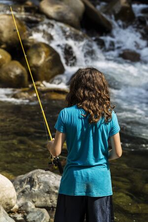 Young girl fishing in rapids of stream for trout during summer day  photo