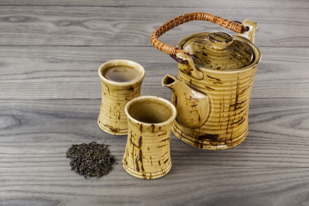 Fresh pot of green tea with dried green tea leafs and cups on white ash wood background  Imagens