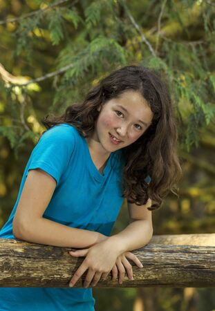 preteen: young girl leaning on log with evergreen trees in background