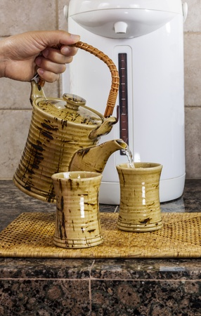 kitchen counter top: Hand pouring tea into cup on kitchen counter top with hot water dispenser in background  Stock Photo