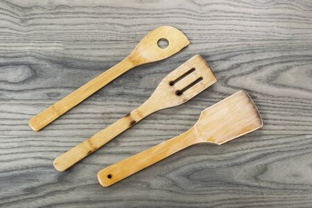 Three wooden spatulas on fading white ash wood background  photo