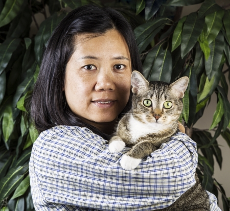 Mature Asian Women holding family cat with plant in background  photo