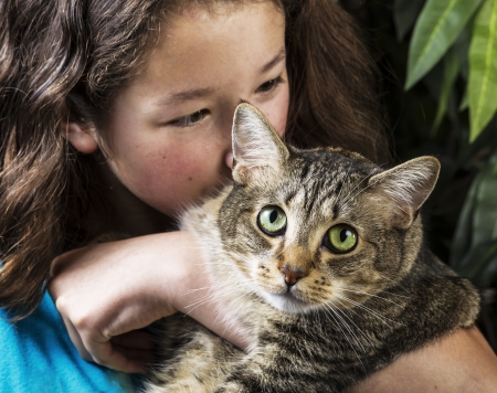 Young Asian girl cuddling tabby cat with green plant in background  photo