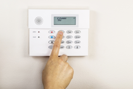 Hand setting the away code on home alarm security panel  Stock Photo