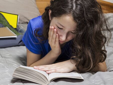 preteen asian: Young girl doing homework assignment while relaxing in her bedroom