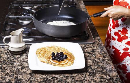 Freshly made pancakes with blueberries on top with frying pan in background  Stock Photo - 15261542