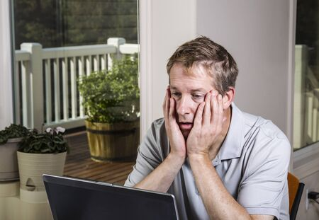 telework: Tired man looking at data results on computer at home