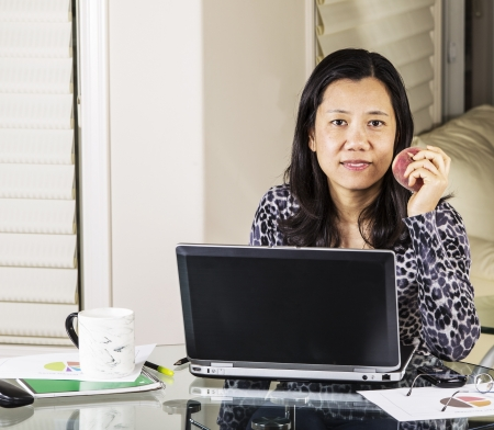 telework: Mature women having snack while at work in home office Stock Photo