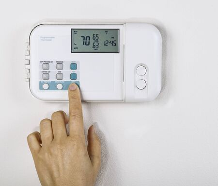 energy save: Hand adjusting inside home temperature to seventy degrees fahrenheit with White wall as background