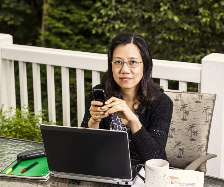 Mature women working outdoors from deck with trees in background Stock Photo - 15544551