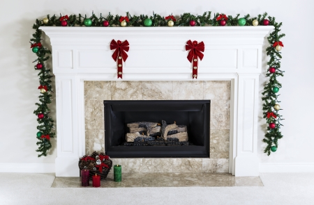 christmas fireplace: Natural Gas Fireplace decorated with Christmas ornaments, candles and basket of dried pine cones for the holiday season