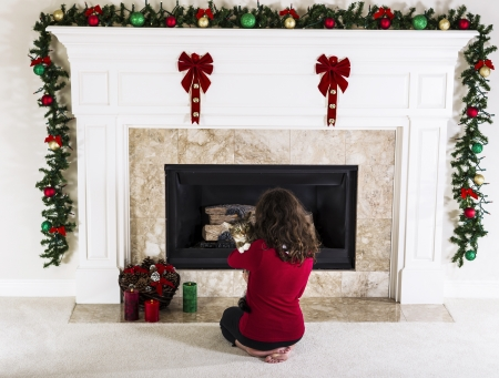Young girl holding family cat in front of holiday decorated natural gas fire place in living room of home  版權商用圖片