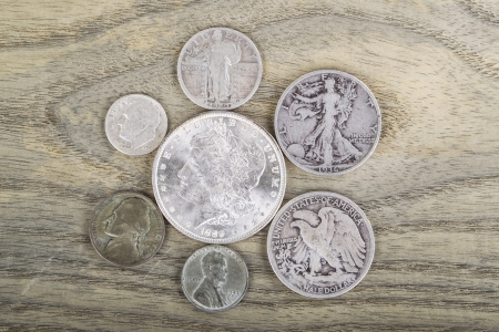 Old Silver Coins on faded white ash wood background  Stok Fotoğraf