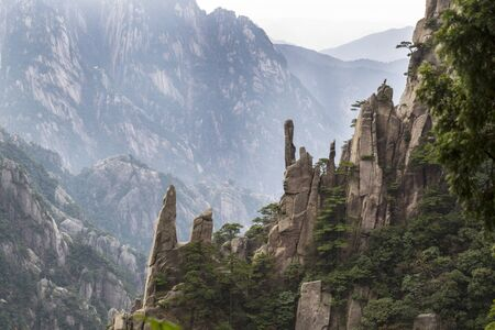 Large Vertical rocks in Chinas Yellow Mountains with misty sky in background