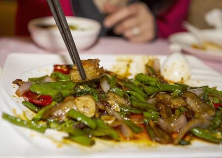 Chinese food dish with chop stick picking food with hand in background