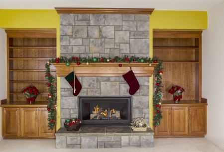 gas fireplace: Large Natural Gas fireplace decorated for the holidays with accent yellow wall in background