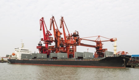 dockyard: Large empty cargo ship docked with cranes and sky in background  Stock Photo