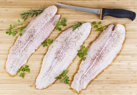 Three skinless fillets of white fish on natural bamboo board with Fillet Knife  photo