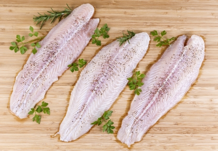 Three fresh white fish fillets with seasoning and herbs on bamboo board  photo