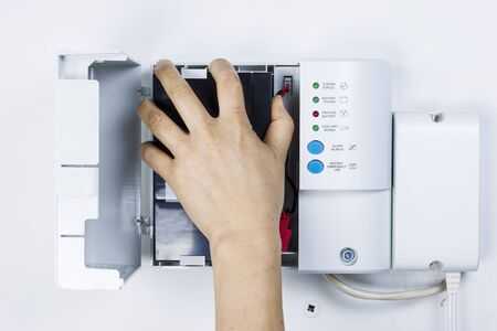 Female hand replacing large backup home battery from unit on garage wall outlet  Stock Photo - 16587610