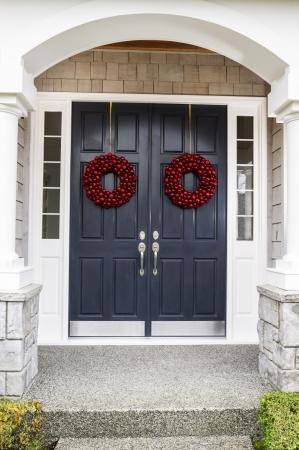 휴가를위한 빨간 공을 화환으로 장식 된 집 문 앞 입구 스톡 콘텐츠