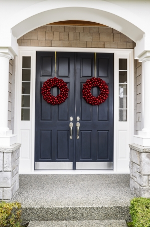 Front entrance of home door decorated with red ball wreaths for the holiday photo