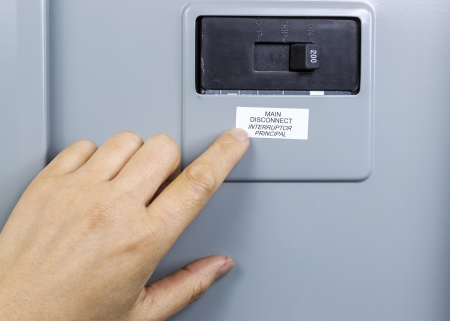 Female hand near main circuit breaker of house power panel photo
