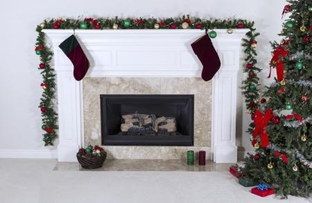 chemin�e gaz: Foyer au gaz naturel d�cor� avec des arbres, des ornements, des bas, le panier et cadeaux Banque d'images