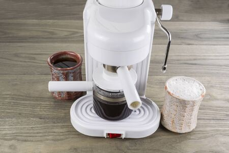 with coffee maker: Espresso maker with drip black coffee and whipped latte coffee on wooden table