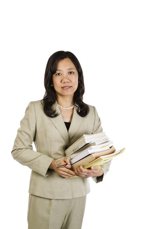 business attire teacher: Mature Asian woman teacher holding stack of books and glasses on white background