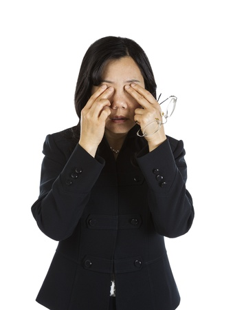 Mature Asian Woman rubbing eyes and holding glasses on white background  Stock Photo