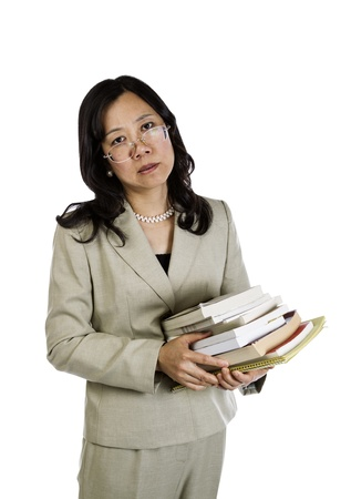 over worked: Mature Asian Woman being over worked holding stack of books on white background