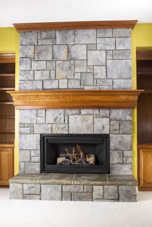 stone fireplace: Natural Gas fireplace built with stone and wooden mantels in family room of modern home