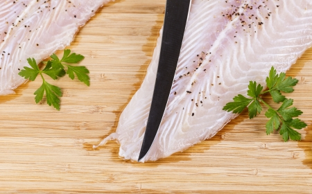 tip of fillet knife on top of white skinless fish with spices and parsley on bamboo board  photo