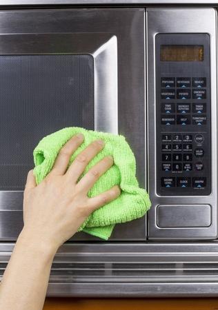 microwave oven: Mano con un trapo de microfibra para limpiar fuera del horno de microondas