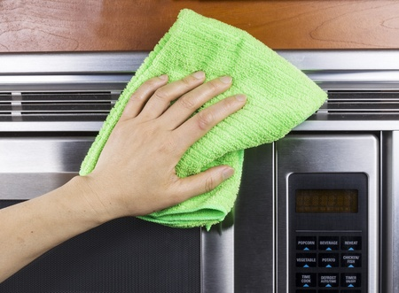 Hand with microfiber rag cleaning vents of microwave oven Stock Photo