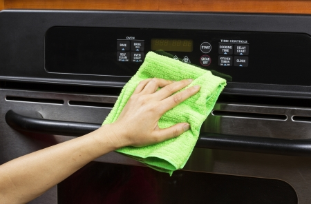 house chores: Hand with microfiber cleaning rag wiping outside of electric oven
