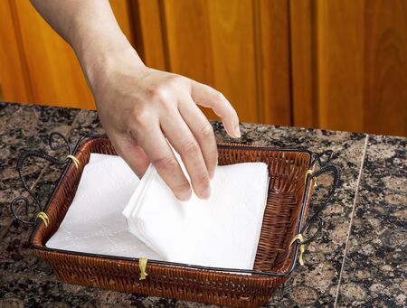 kitchen counter top: Hand picking up paper napkins out of basket on kitchen counter top  Stock Photo