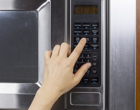 defrost: Hand preparing to activate defrost mode on microwave oven Stock Photo