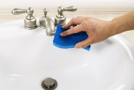Hand with sponge cleaning bathroom sink faucet Banco de Imagens