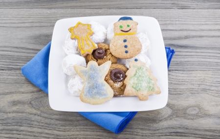 Variety of homemade holiday cookies in white plate on faded wooden table with blue cloth napkin Imagens
