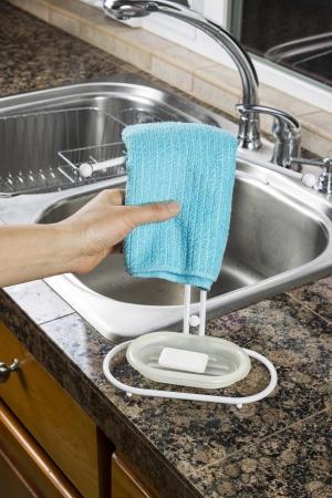 microfibra: Mano femenina que cuelga una toalla de microfibra plato en la parrilla en la cocina