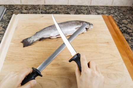 sharpen: Female hand sharpening fillet knife with single fish on cutting board