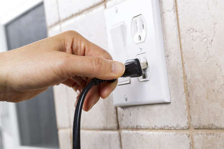 Female hand plugging in appliance to electrical outlet in wall Stock Photo - 17008067